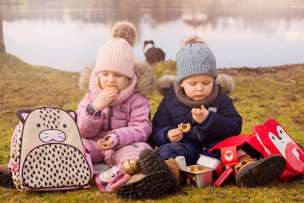 två barn med smartwatch som äter kex ute